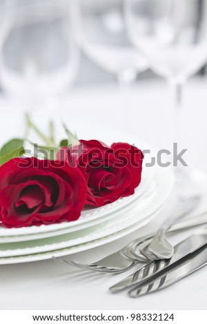 Romantic table setting for two with roses plates and cutlery