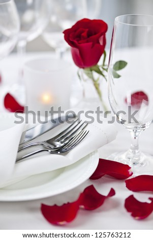 Romantic table setting with rose petals plates and cutlery #125763212