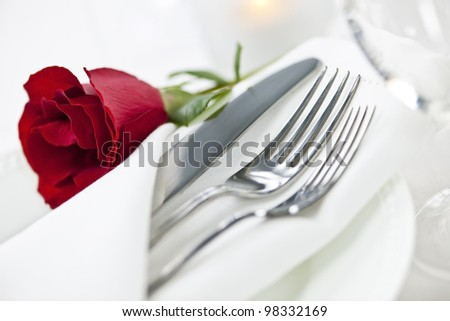 Romantic table setting with rose plates and cutlery