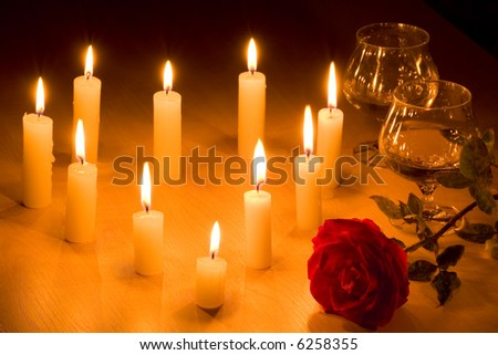 Romantic table with flaming  heart of candles, two glasses of wine and red rose.