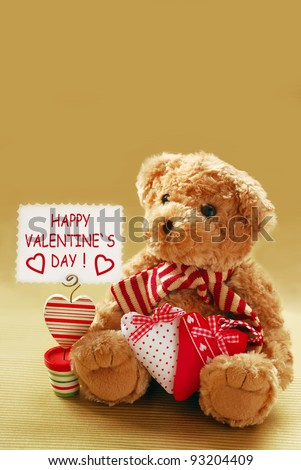"romantic teddy bear with ""happy valentine`s day"" banner against golden background"