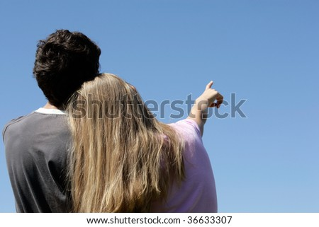 Romantic teenage couple looking at blue sky. Girl pointing.
