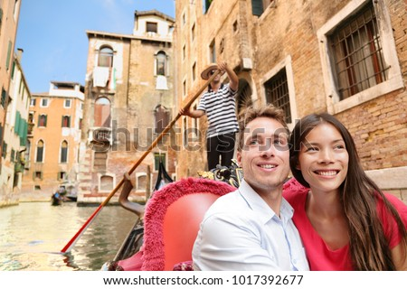 Romantic travel couple in Venice on Gondola ride romance in boat talking happy together on travel vacation holidays. Young multiracial couple sailing in venetian canal in gondole. Italy, Europe