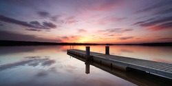 romantic travel place, beautiful sunset on wooden jetty at the lake