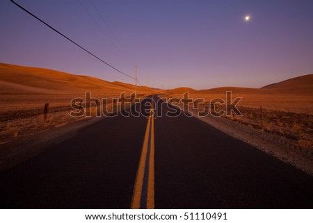 Romantic two lane country road at dusk in farm land country - idyllic dusk / dawn lighting.