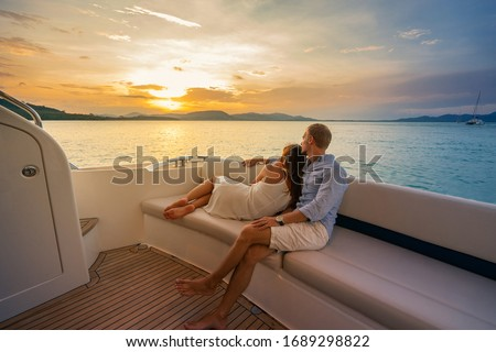 Romantic vacation . Beautiful couple looking in sunset from the yacht. Stock photo ©