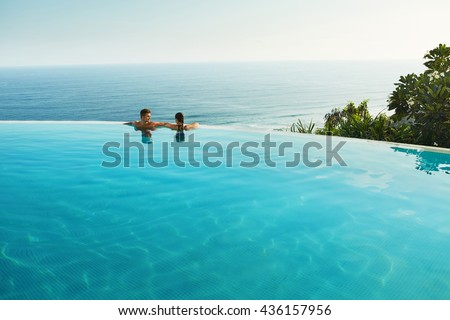 Romantic Vacation For Couple In Love. Happy People Relaxing In Infinity Edge Swimming Pool Water, Enjoying Beautiful Sea View. Man, Woman Together On Summer Travel To Luxury Resort. Summertime Relax