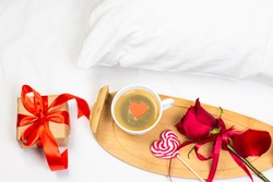 Romantic Valentine's Day or holiday breakfast in bed with cup of coffee, heart shape lollipop, gif box, and red rose. Top view, flat lay image.