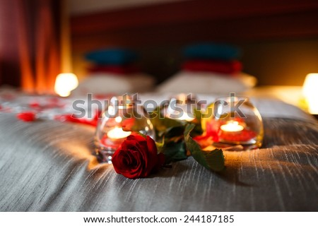 Romantic Valentines Day evening. Romantic night. Rose and candles on bed.