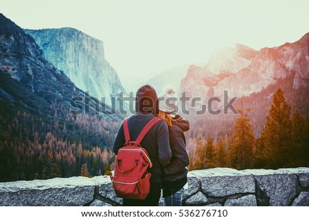 Romantic view of a young couple enjoying famous Tunnel View in beautiful golden morning light at sunrise in Yosemite Valley in summer with retro vintage Instagram style filter effect, California, USA