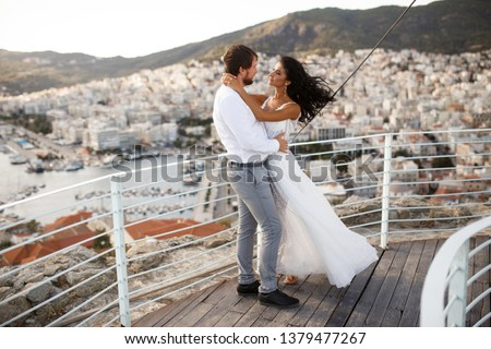Romantic view of romantic couple in white clothes, when they cuddle on green grass. Beautiful landscape of sun above mountain and city during sunset. Concept of honey moon love.