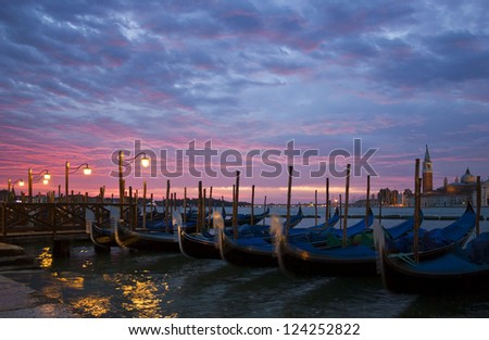 Romantic view of Venice with lampposts and gondolas near San Mark's Square with an early morning sunrise and San Giorgio Maggiore at the background.