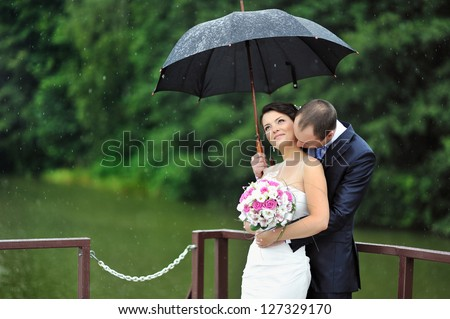 Romantic wedding couple kissing in a rainy day
