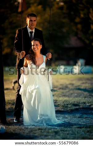 Romantic wedding couple sitting on a swing in nature