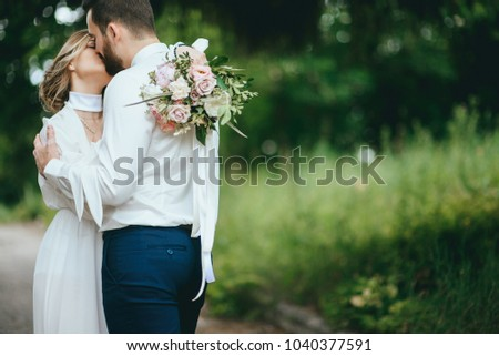 Romantic wedding moment, couple of newlyweds smiling portrait, bride and groom hug while on a walk in the park