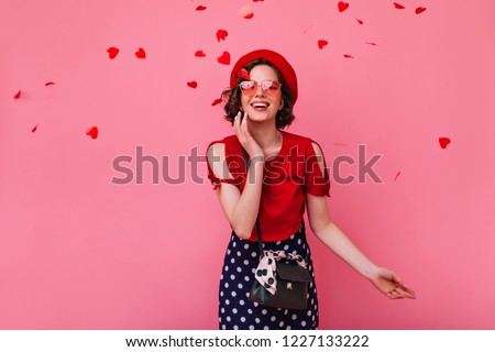 Romantic white woman with brown hair expressing happiness in valentine's day. Enchanting stylish girl in funny glasses posing on rosy background with confetti.