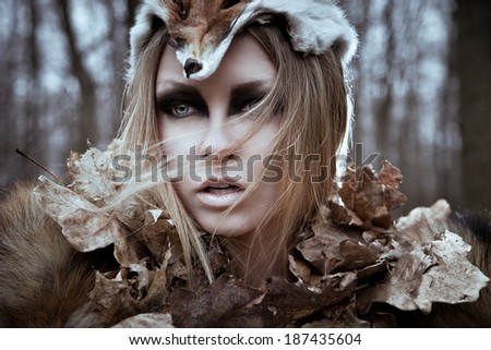 Romantic wild beauty tribal woman in fox costume in wild forest. Vintage styled