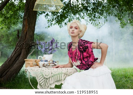 Romantic woman on a picnic in a fairy foggy forest. Outdoors.