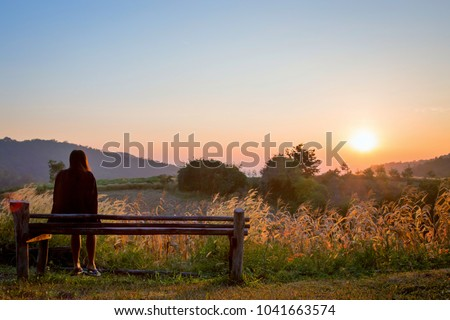 Romantic woman sitting on the wooden chair.Asian girl looking at sunrise in the morning on mountain ,Suphanburi province,Thailand.Lonely girl with nature concept. #1041663574