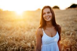 Romantic woman walking in golden fields of barley