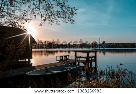 romantic wooden boat dock with boat at the lake Evening mood, evening light #1388256983