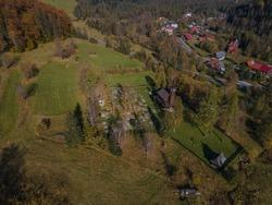 Romantic wooden church in Tatranská Javorina, Slovakia, with panoramic view of Tatra Mountains, early autumn