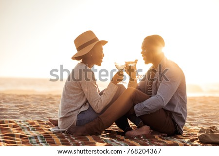 Romantic young African couple toasting each other with wine while sitting together on a sandy beach at dusk