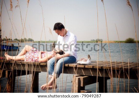 Romantic young asian couple in love sitting on pier.