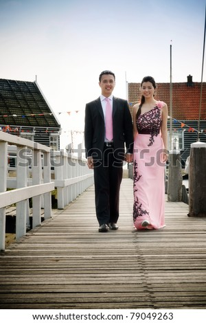 Romantic young asian couple in love walking on pier.