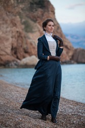 Romantic young beautiful lady wearing victorian dress looking  at the sea. Vintage style. Steampunk concept