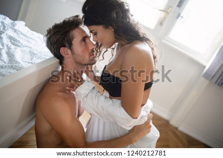 Romantic young couple being intimate and sensual in bedroom