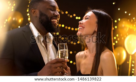 Romantic young couple clinking champagne and smiling each other, having fun #1486139822