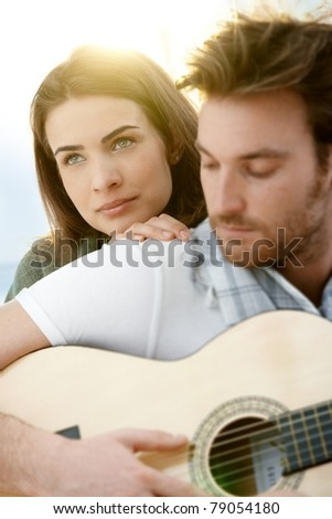 Romantic young couple embracing playing guitar outdoor in summer sunlight. Woman in focus.?