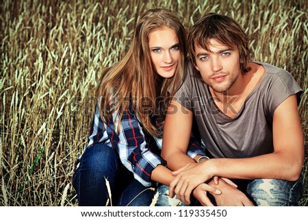 Romantic young couple in casual clothes sitting together in a wheat field.