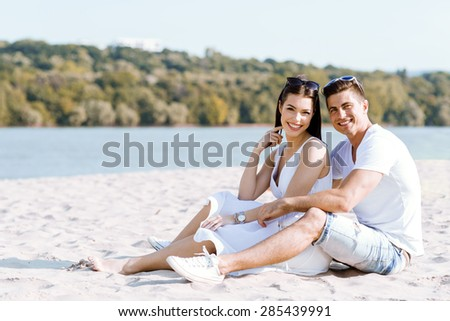 Romantic young couple in love sitting at a sandy beach and smiling