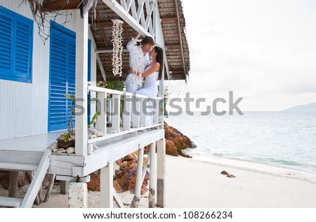 Romantic young couple in tropical beach house