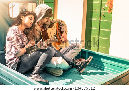 Romantic young Couple of lovers playing Guitar outdoor after the Rain