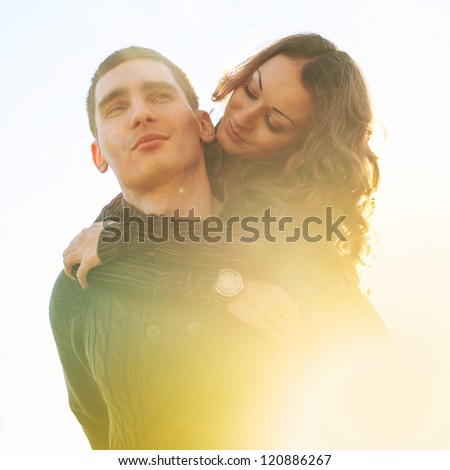 Romantic young couple outdoors with back light.