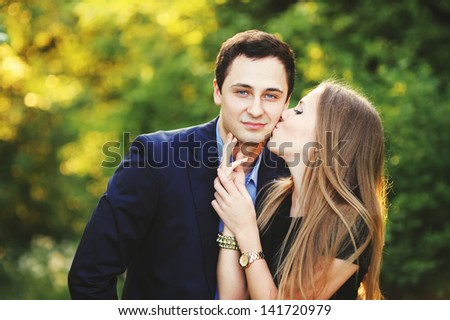 romantic  Young couple outside, young woman kissing her boyfriend - stock photo