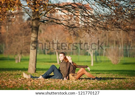 Romantic young couple relaxing outdoors in autumn park.