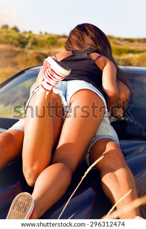 Romantic young couple sharing a special moment while on a road trip.Man driving car with girlfriend.Sexy girl laying on car and kissing her boyfriend,cool outfit,having fun,sunny,man woman together