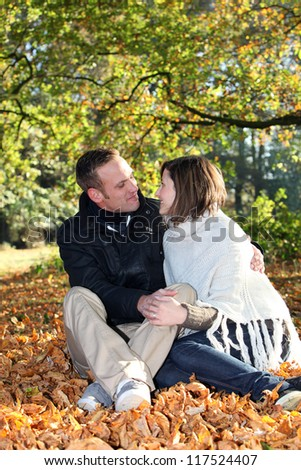 Romantic young couple sitting in a close embrace gazing amorously into each others eyes while seated amongst fallen autumn leaves in a forest