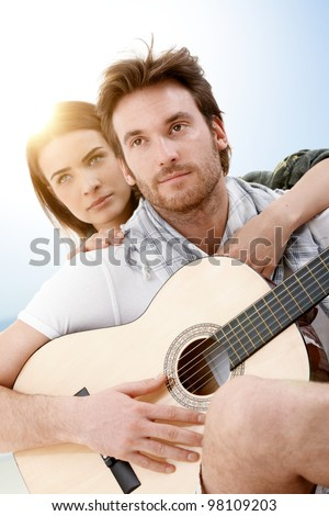 Romantic young couple sitting on beach in summer sunlight embracing, playing guitar. - stock photo