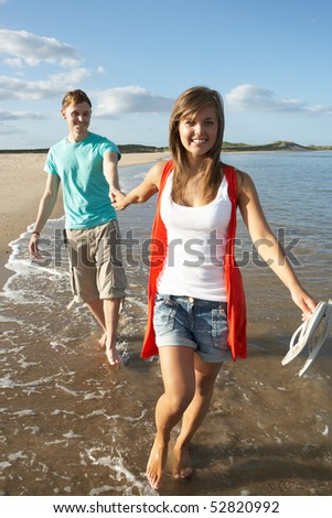 Romantic Young Couple Walking Along Shoreline Of Beach Holding Hands