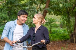 Romantic young couple with bicycle looking each other while walking in the park. Happy young woman blond hair laughing hold bike while talking with her boyfriend feeling enjoying at autumn park.