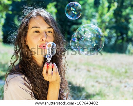 romantic young girl inflating colorful soap bubbles in park