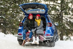 Romantic young hipster couple hugging while sitting in car trunk under falling snow. Love, valentines and holiday concept. Kiss and hug. Valentines day celebration and happiness concept