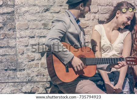 romantic young man play guitar sing love song while amused shy girl smiling. concept of love and romance.