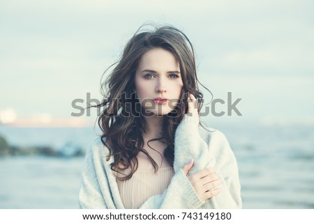 Romantic Young Woman on Blue Natural Background Outdoors