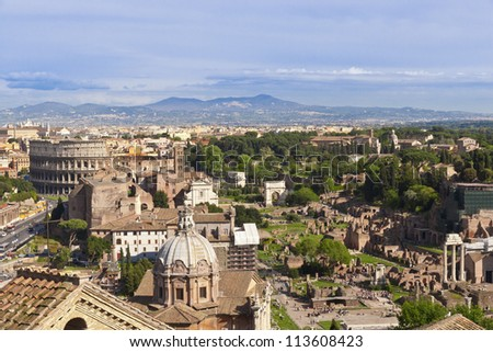 Rome cityscape with view of Colosseum and Roman Forum ruins.